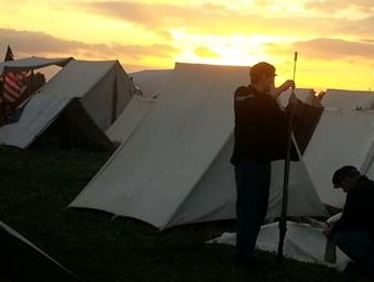 Reenactor cleaning rifle as the sun rises.